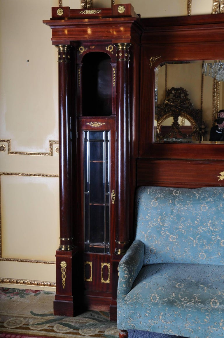 Mahogany on solid wood. Architecturally designed body flanked by solid columns. Facet-ground mirror and glass panes. Gilded bronze fittings. In the middle a two-seat sofa.   (O-248).