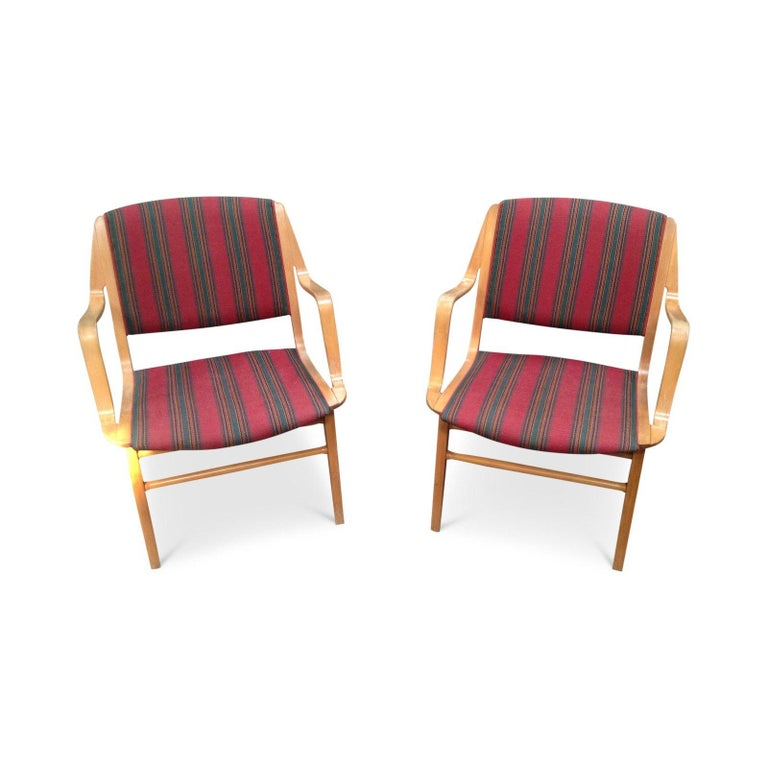 Beautiful vintage European armchairs. Untouched and in original condition. They have a wooden frame accented with uniquely colorful upholstery. Bound to make a statement in any space.