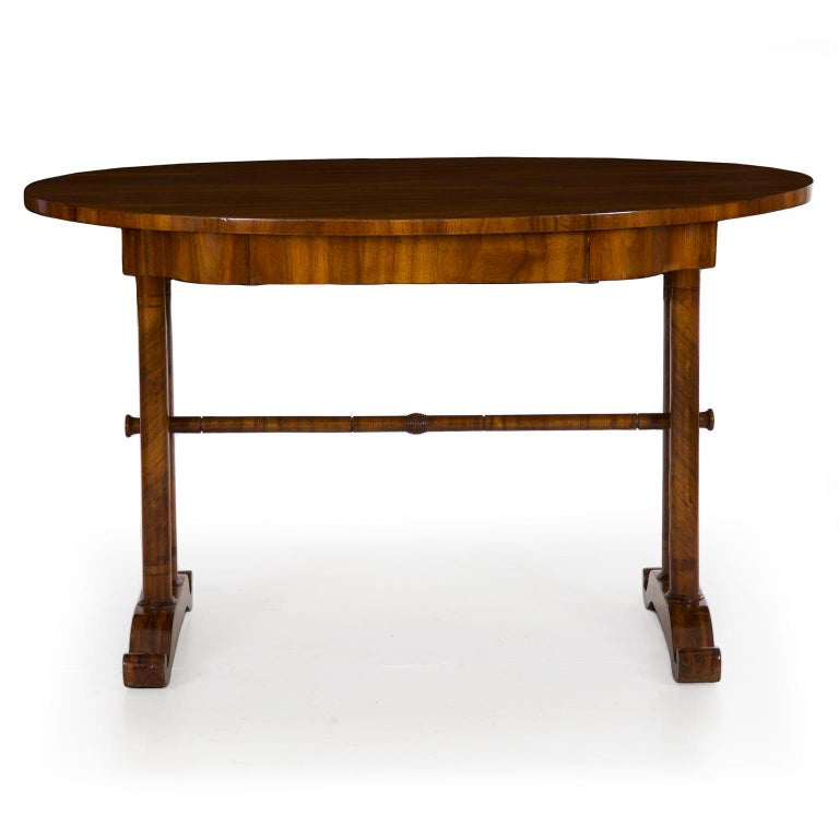 A fine austere writing table from the second quarter of the 19th century, likely Austrian or possibly German, the stand is distinctly Neoclassical with its twin columns and cupid's bow footing. The veneer work is excellent with a spiral wrap of