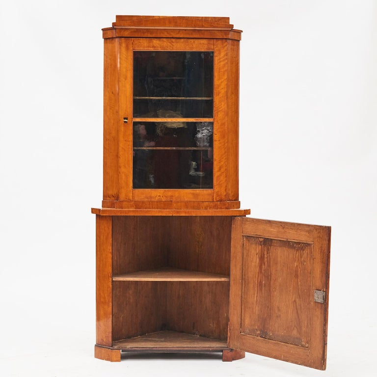 Biedermeier corner cabinet. Vienna, Austria, circa 1820-1830.  Pine veneered with flamed birch wood, beautiful grain and glow. Original condition with a light polished finish. The cabinet is in two parts, upper part with 1 glass door, lower part