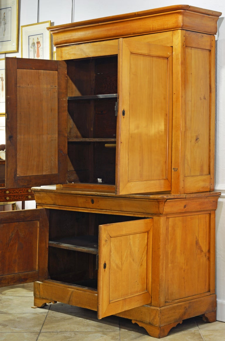 This honey colored Austrian fruit wood step back cupboard features an upper section with two doors opening up to a shelved interior and a slightly bigger lower section with a long frieze drawer, two doors and one shelf. It is topped by a molded