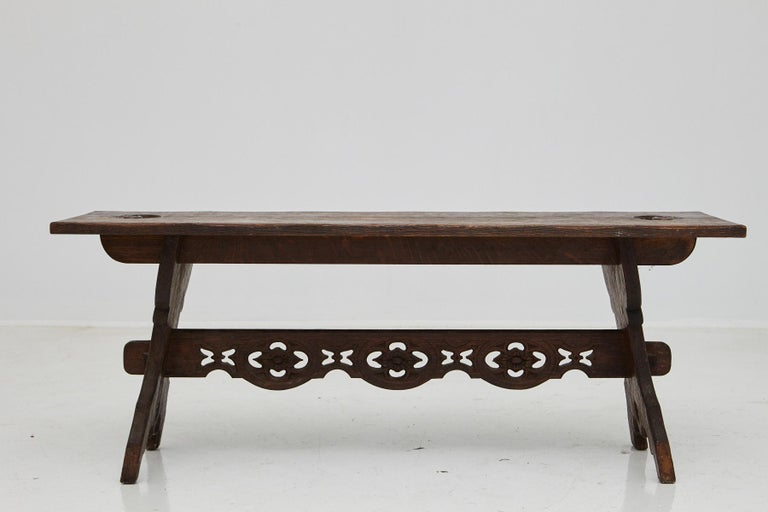 19th century Austrian hand carved rustic trestle oak bench, with carved details in the trestle and two carved handles at the top of the bench. Very good condition, normal scratches from usage, great patina.