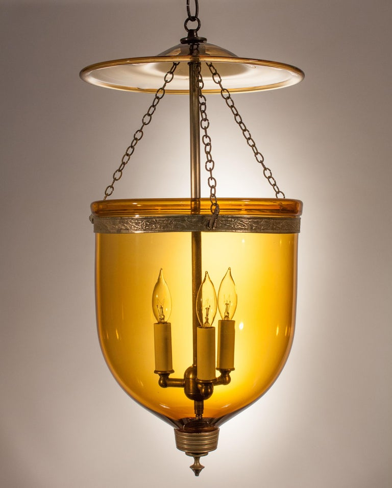 A rich amber-colored hand blown glass bell jar lantern with its original embossed brass band, finial and glass smoke bell. Chains are replaced, but originals are available. At first used with candles, this circa 1880 lantern has been newly re-wired
