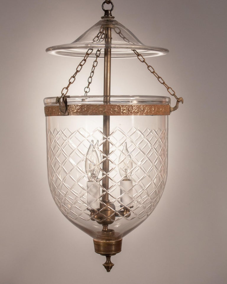 Handblown glass bell jar lantern from England, circa 1860, with a lovely funneling form and an etched diamond motif. The embossed brass band and unadorned finial are original to the hall lantern. The smoke bell, or lid, is period. The pendant has