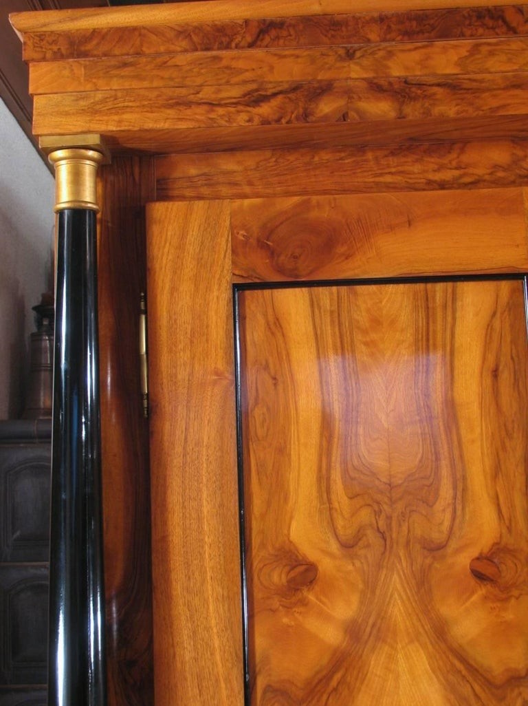 Classic example of a Biedermeier armoire dating back to the early phase of the Biedermeier style. Beautiful walnut veneer on sides and doors. The doors are flanked by ebonized columns. The interior cabinet set up with a hanging rail and shelfs has