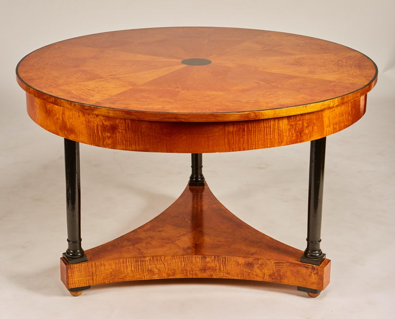 Beautiful early 19th century Biedermeier center table or round dining table with ebonized columns, pie shaped burl veneer inlay with ebonized center point decoration. Older restoration, shows well, minor scuffs to top.
