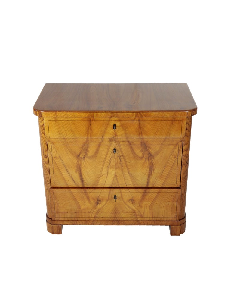 The Biedermeier chest of drawers with 3 drawers, designed in a straight line but with slightly curved edges, was created, circa 1830-1840. The drawers differ in size and are elegantly framed by a fine ebonized wood inlay the chest of drawers is in