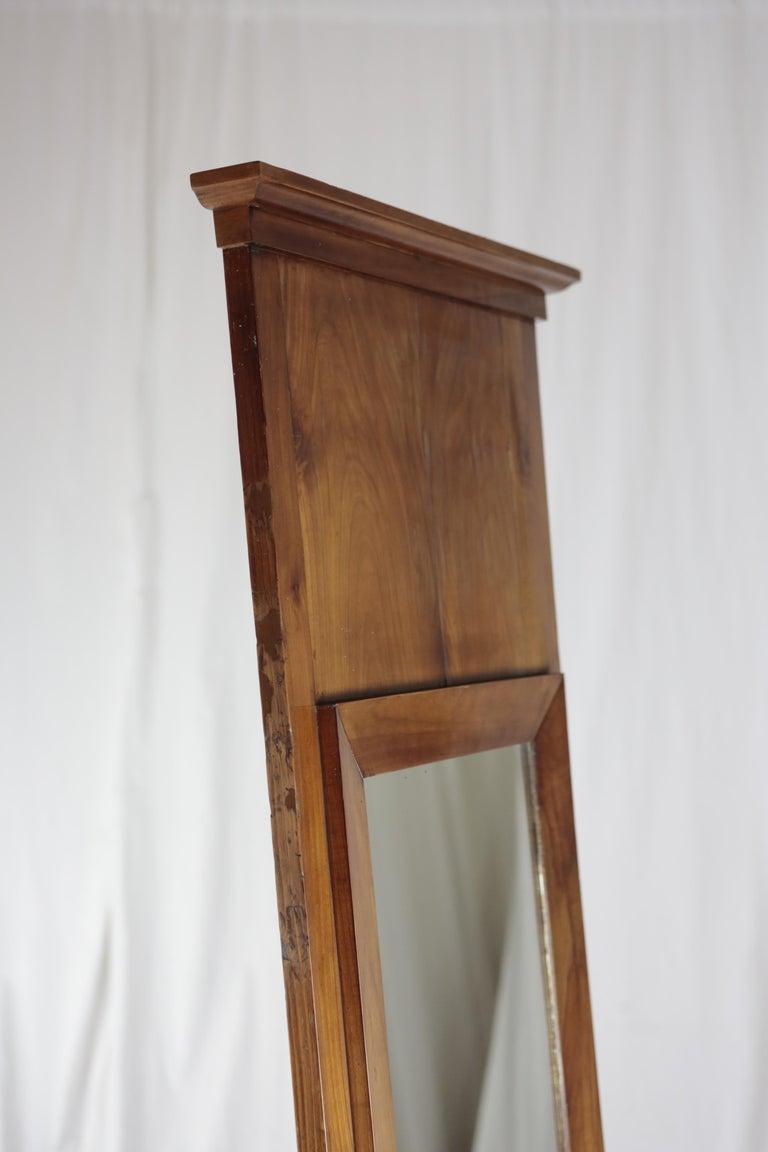 Biedermeier pillar mirror, circa 1830 Cherry tree veneered, veneer nicely mirrored Old reflecting glass Restored residential-ready state French Shellac hand polish. Measures: Height 189 cm, width 65 cm, depth 6 cm.