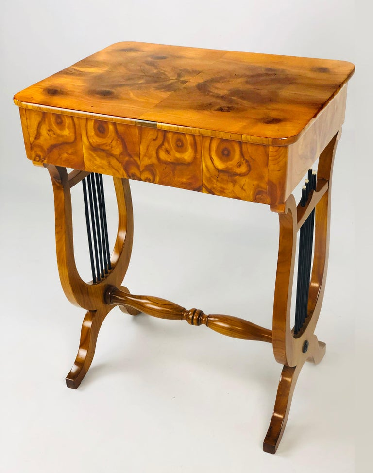 Outstanding early 19th century German Biedermeier sewing side table with twin lyre base, the top and aprons adorned with rare oyster walnut veneer. The single drawer has several small compartments and an original folding needle cushion. The top is