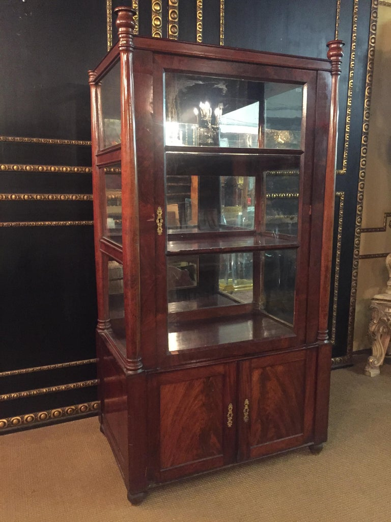 Three-sided glazed glass vitrine circa 1825 in the sense of Karl Friedrich Schinkel. High-quality Mahogany on solid softwood. Recessed frame box. Architecturally arranged front with flanking columns, Three-sided sprout-glazed corpus. Stepped
