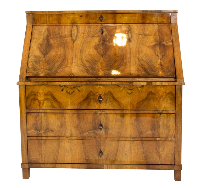 The Biedermeier secretary is covered with walnut veneer with a beautiful veneer pattern. This furniture originates from Germany, circa 1825. The interior of the secretary is also decorated with walnut, maple and ebonized elements. In very good