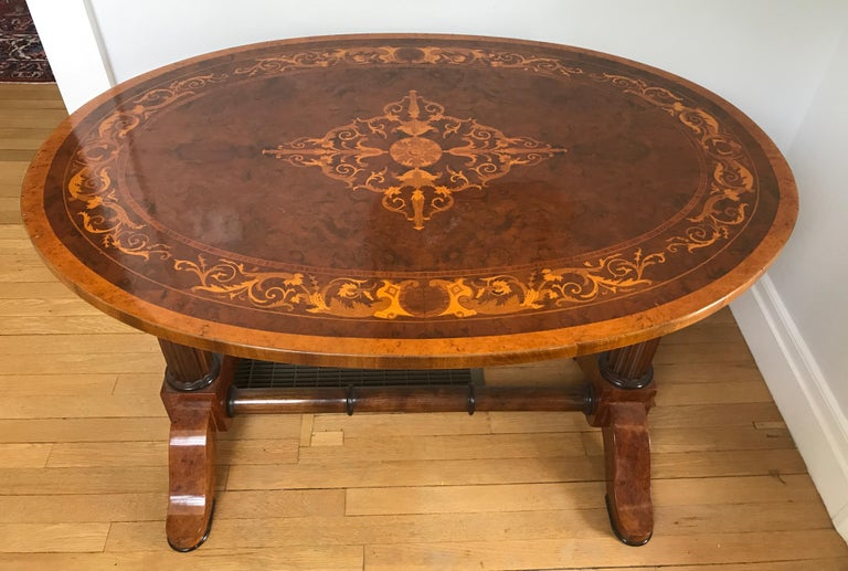 Unique oval 19th century Biedermeier writing table, Hungary circa 1820-1830, bird's-eye maple veneer, burl walnut and elmwood veneer with akanthus leave marquetry on the top. The table has one drawer. Great design with beautiful details. The table