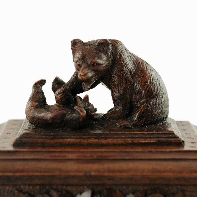 This unusual antique Black Forest box features a pair of fully dimensional bears cavorting at the base of a tree stump. The mother and cub have been finished with a high level of detail including glass eyes in the larger bear's head. The bears are