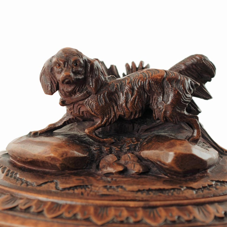 This 19th century Black Forest carved wood lockable casket has an oval shape and is topped with hinged lid featuring a fully dimensional carved spaniel with glass eyes. The dog has been depicted posed atop two rocks amongst vegetation with its mouth