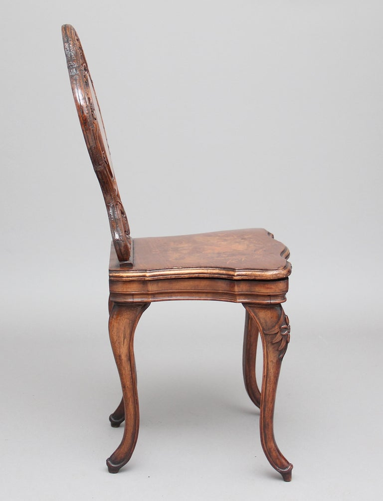 19th century Black Forest musical chair in walnut, the profusely carved back with an inlaid central panel and also an inlaid panel on the seat, depicting typical Swiss scenes, standing on four carved swept legs, circa 1890.