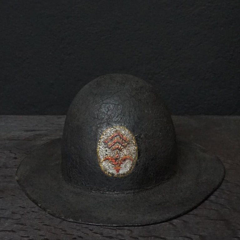 19th century black painted leather French fire helmet with painted logo with what looks like a 'French Lily' and three hooked lines Made out of one piece of hardened and painted leather, soft leather lining held together by a (not original)