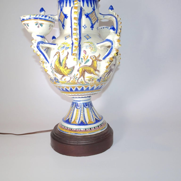 This 19th century blue and white delft table lamp with four handles and two small bowls. The pattern on the delft lamp has animals and a stylized pattern in shade of blue and gold.  A shade is available is you want to ship separately.  A nice finial