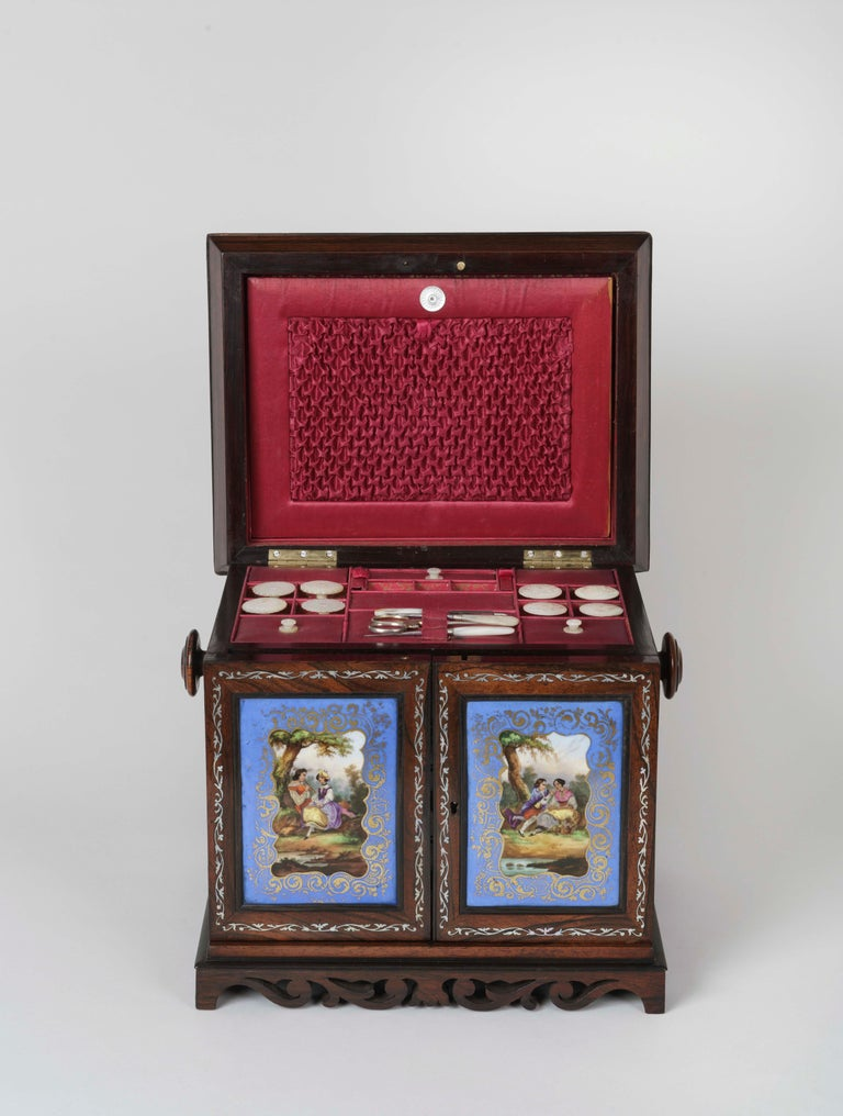 A Fine Table Cabinet  Rising from scrolling foliate bracket feet, the rectangular cabinet constructed in rosewood and surmounted with a hinged cavetto moulded lid set with a Sèvres-style porcelain plaque and a mother-of-pearl inlaid border, the lid