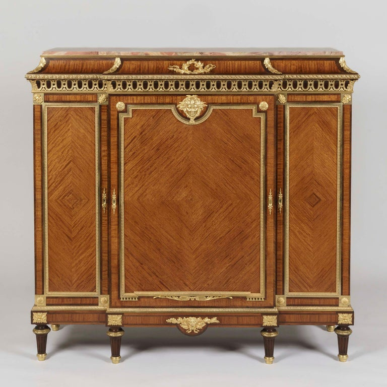 A Bois Citronnier Meuble d'Entre Deux By François Linke  Constructed from satiné quarter-veneered bois citronnier, with rosewood crossbanding and ormolu mounts, the rectangular cabinet of slight breakfront proportions supported on tapering feet,