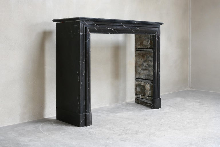Beautiful antique fireplace made of black marble. This black marble type is called Nero Marquina and has a beautiful black color with light veins. A unique fireplace, because it is a natural product and every natural product is different. This
