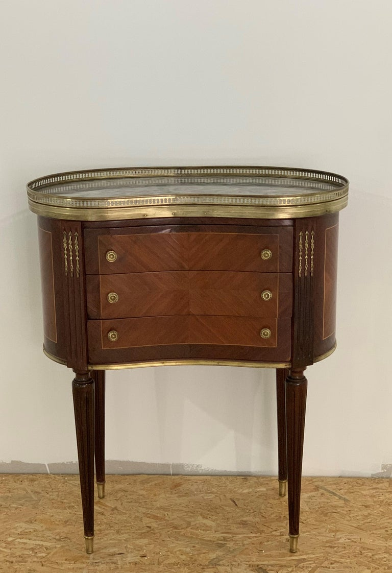 French Louis XVI style side table or nightstand topped with a grey marble, fluted legs finished with golden bronze clogs. One dovetailed small drawer with brass details.