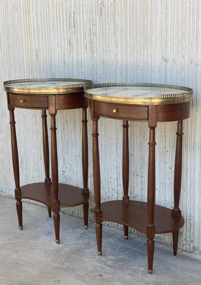 French Louis XVI style side table or nightstand topped with a beautiful white marble, fluted legs finished with golden bronze clogs. One dovetailed small drawer with brass details.  Merasures: Total height 27.55in Height to the high shelve