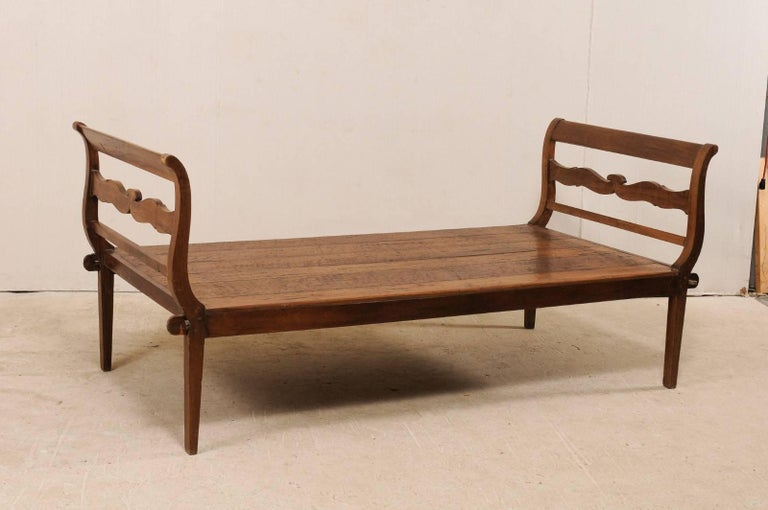 A Brazilian 19th century peroba wood daybed. This nicely-sized antique daybed from Brazil features curvy slatted head and foot boards, with a beautifully carved center slat. The peroba wood, which is a tropical native hardwood to Brazil that is 35%