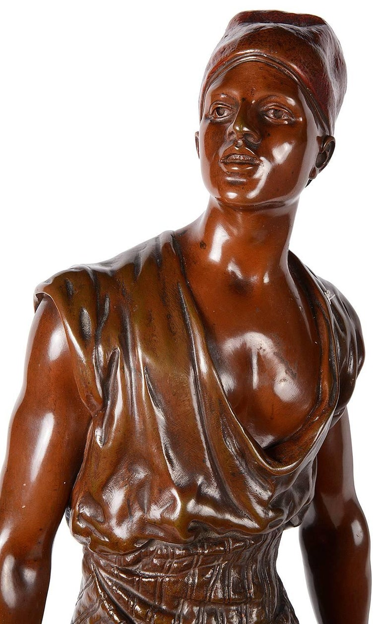 A good quality 19th century bronze statue of an Arab water carrier, having a good patina, signed; Debut and a plaque reading;