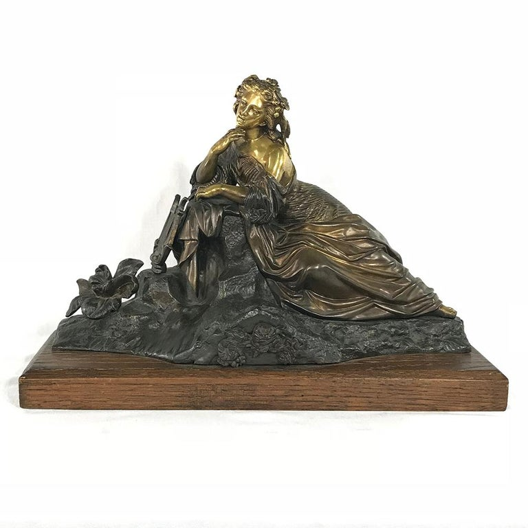 19th century bronze D'Or Statue depicts a beautiful maiden in luxurious clothing during a pensive pause from her playing the lyre. The sculptor has laid a