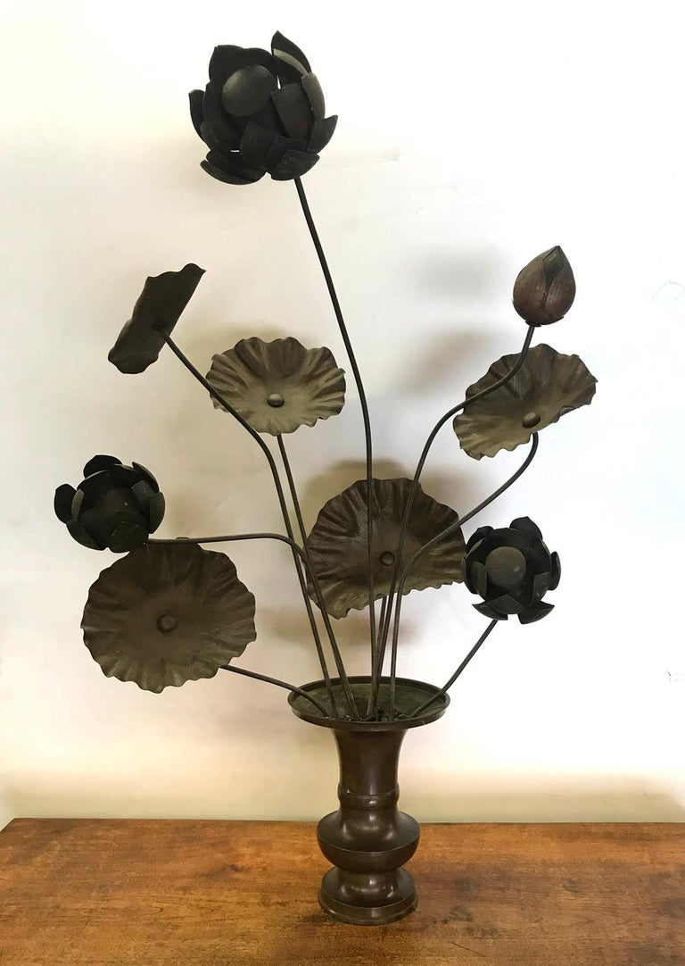 Nine hand sculpted bronze lotus flowers in one of two bronze vases. These originally sat in a temple in Kyoto. Dark original patina, beautiful detail on flowers and petals. Graceful and elegant. Can arranged freely within the vase, or removed from