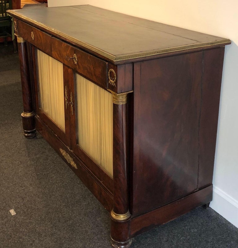 19th century French Empire cabinet with bronze mounts and leather top. 2 drawers over 2 door cabinet.