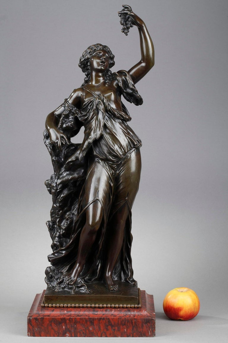 This statue featuring a Bacchante is crafted of patinated bronze. In Roman mythology, Bacchae, or Bacchantes, were the female followers of Bacchus. They were often depicted in the company of Satyrs, dancing, playing tambourines and cymbals.
