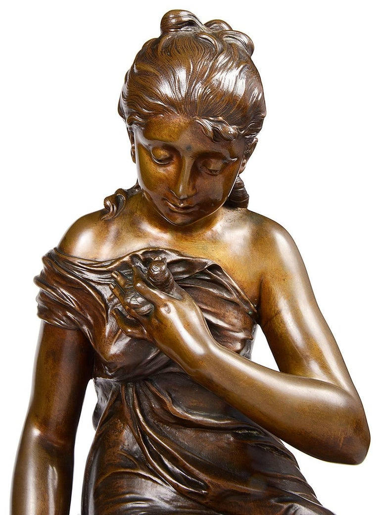 A charming 19th century bronze statue of a young girl seated on a rock hold two small birds. Signed; Lx. Richard.