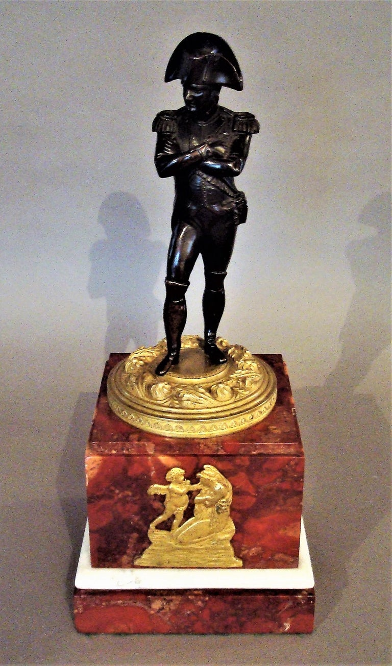 Good 19th century bronze statue of Napoleon Bonaparte on an impressive marble plinth; Napoleon with his arms folded in Classic military dress; standing on an ornate circular ormolu socle of foliate and anthemion design; raised on a bold Griotte
