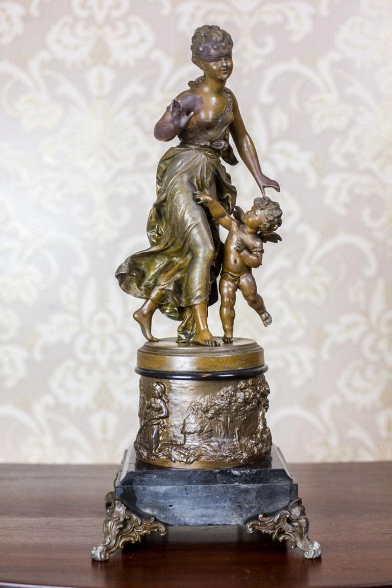 This figurine, dated fourth quarter of the 19th century, depicts a young girl playing with a putto.