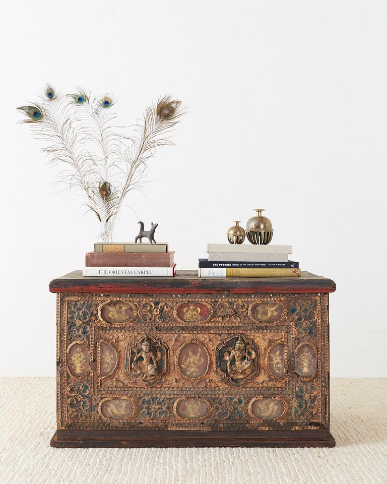 Fantastic 19th century Burmese Mandalay period chest or trunk. Decorated with Buddhist gilt relief carvings on the front with some incased in glass. Intricate gilded metal borders and glass mosaics adorn the windows. The chest has a flip top to