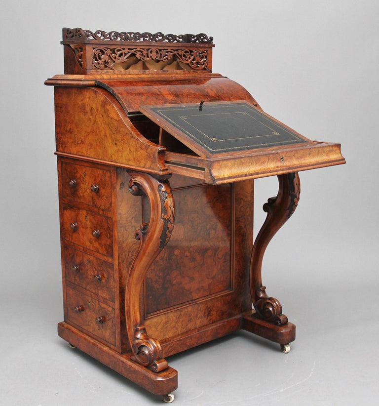 A superb quality 19th century freestanding burr walnut rising top davenport, the moulded edge top decorated with carved fretwork, this section rises up from the desk which shows more intricate carved fret work which lifts over to reveal various