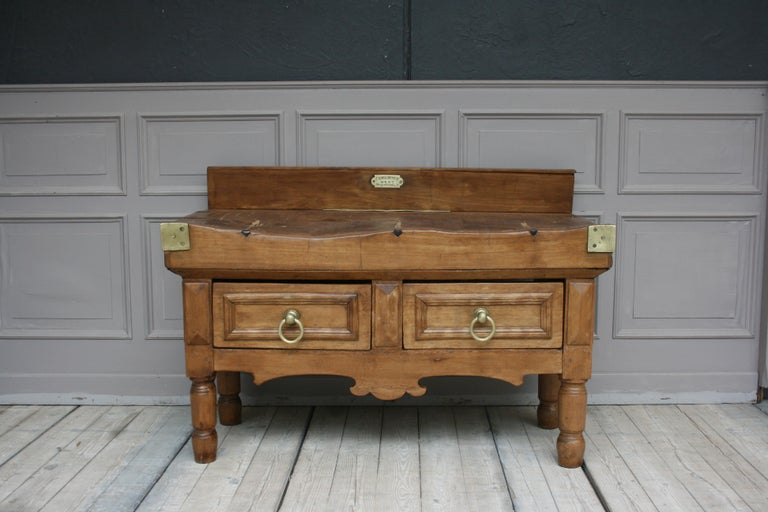 A large late 19th century butcher block table from Belgium. Standing on 4 massive turned feet with manufacturer's badge, brass or bronze fittings and 2 drawers.   Dimensions:  80 or 95 cm (including the backboard) high / 31.5 or 37.4 (including