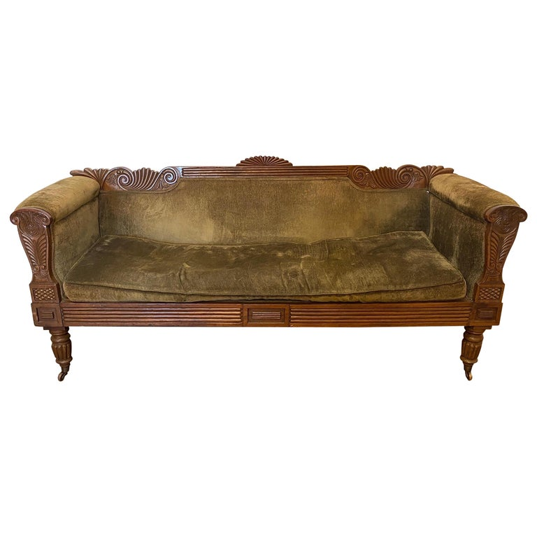 19th century carved English regency sofa with green velvet upholstery and original castors.
