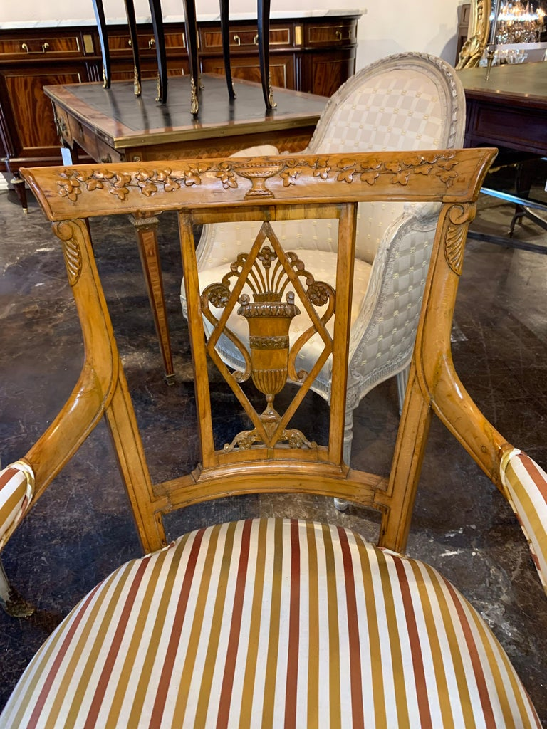 Beautiful pair of carved fruitwood armchairs from England in the neoclassical style. The carvings have an urn with overflowing flowers and vines. The chairs are upholstered in silk with the colors, crème, copper and gold.