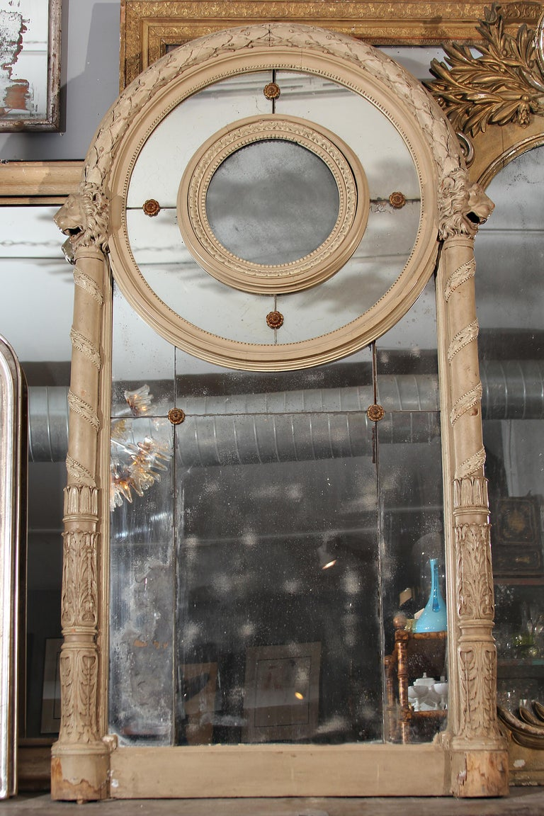 Grand 19th century Italian mirror in original paint with hand carved lions looking outward on each side. Beautiful patina to each mirrored panel.