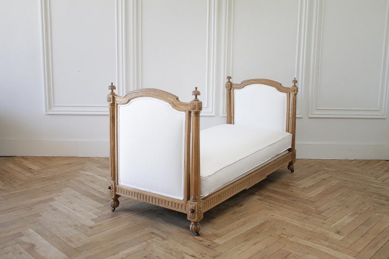 19th century carved natural walnut daybed with white upholstery Original side rails and bolt construction, this daybed is solid and sturdy. Original caster wheels, with carved finials. We reupholstered this in a durable easy to clean white nubby