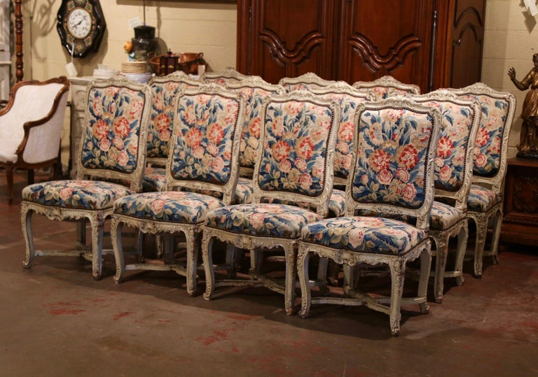 Decorate a dining room with this exceptional suite of twelve antique and colorful chairs; crafted in Paris, France, circa 1820, each large chair stands on elegant cabriole legs decorated with acanthus and floral motifs, ending with escargot feet