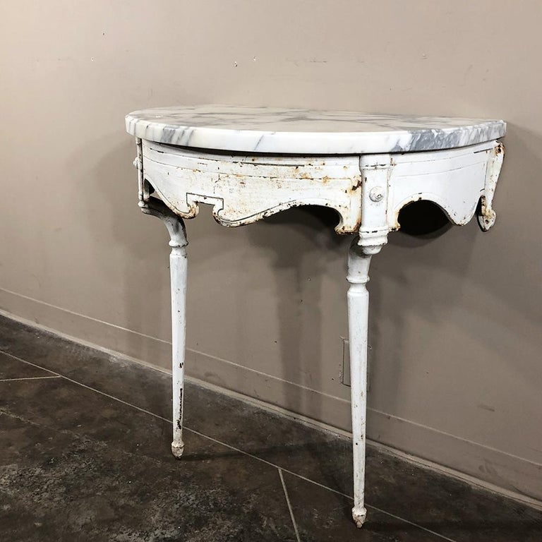 19th century cast iron demilune marble top console represents an unusual find, originally used in conservatory or garden with the framework consisting of intricately detailed cast iron supported by two legs, which requires mounting to the wall. A