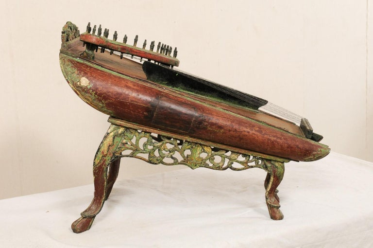 A traditional string musical instrument from Java, late 19th century. This antique celempung from Java, Indonesia has a beautifully decorated wood body, with pierced and carved skirt undercarriage and raised upon legs that terminate into hoof feet.