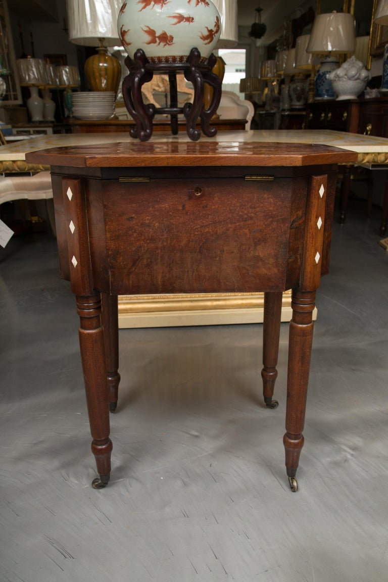 This is a very collectible period Charles X mahogany sewing table. There is a lift top with canted corners and pie-shaped veneers centered by an inlaid checker board above a bank of three drawers with decorative accents. The table is supported by