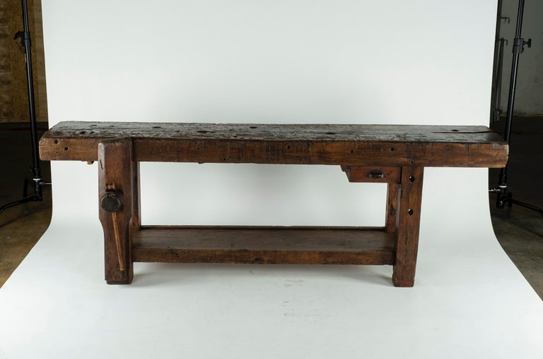 19th century chestnut workbench with original vise and a shelf underneath. The depth of the piece with the vise is 24