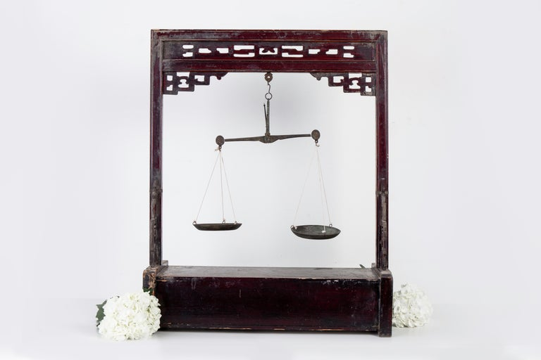 Large Chinese carved wood apothecary balance scale with stand and storage drawer cabinet. It features beautiful carved fretwork on the top and sides featuring brass metal hardware and trim. It is finished in its original dark red lacquer which has