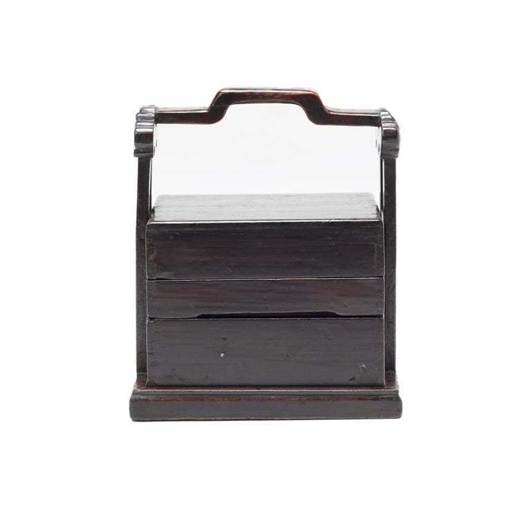 The basic form of this three-tiered rosewood box with handle has remained unchanged for a thousand years. The lack of formal dining rooms in traditional China prompted families to use stacked boxes to carry food from a remote kitchen to the room