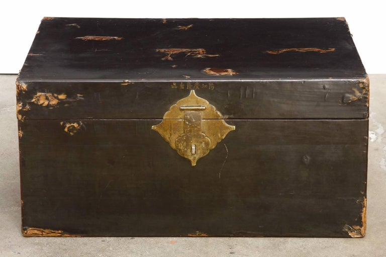 Rare 19th century Chinese pigskin trunk featuring a black lacquered finish. Beautiful distressed patina with a smooth soft finish. Brass-mounted large handles, hinges, and lock plate with original working key. Maker's mark on the inside and Chinese